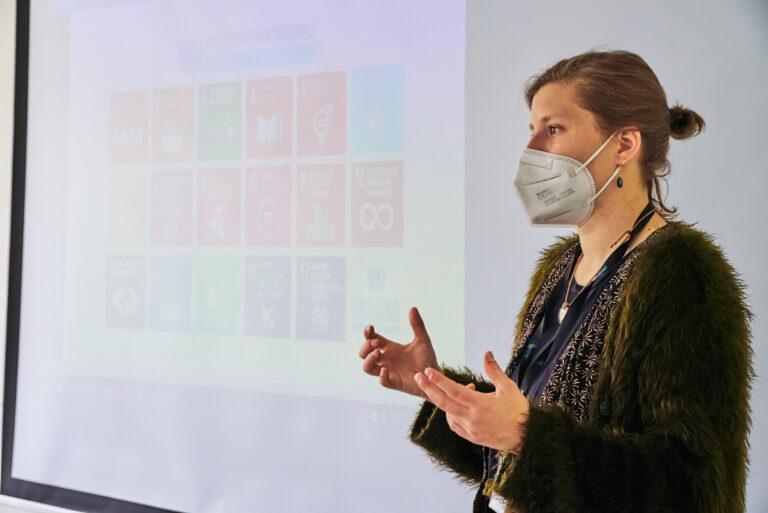 Sophia Bachmann vor einer Leinwand mit den 17 Zielen der UN.
